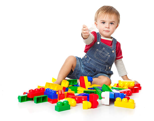 Funny boy is playing with lego stock photo