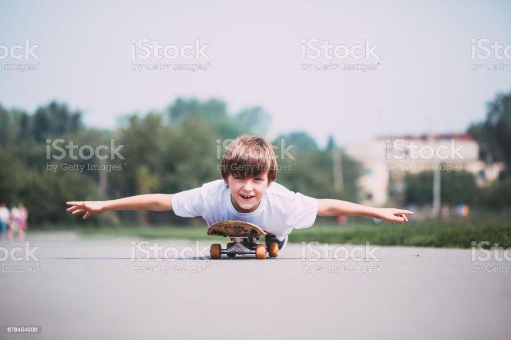 Funny boy lying on a skateboard. royalty-free stock photo