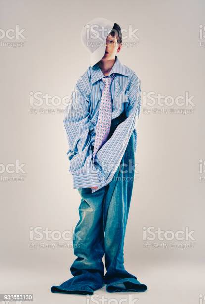 Caucasian boy wearing his Dad's shirt, jeans and tie on light background. He is wearing big adult size clothes which are too big for him.