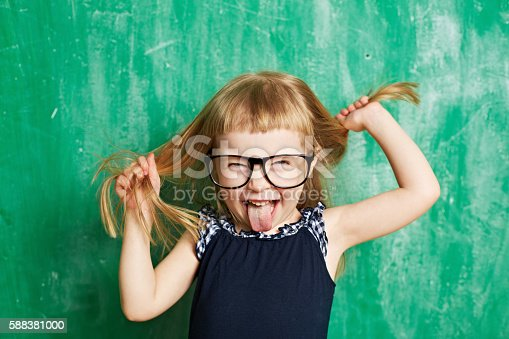 Little child with mischief looking at camera. Cheerful brat holding hair and sticking tongue out. Cute girl wearing eyeglasses. Its photo illustrating childhood. It is perfect for using it in commercial and advertising photography, reports, books, presentation