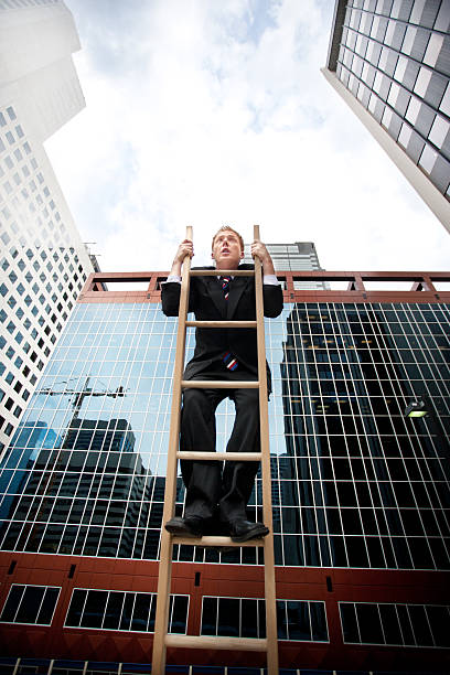 funny businessman Hangs Onto the corporate ladder stock photo