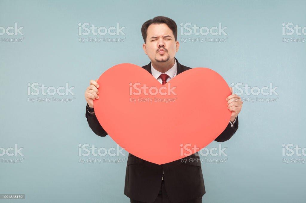 Divertido empresario sosteniendo corazón rojo grande y enviar beso - foto de stock