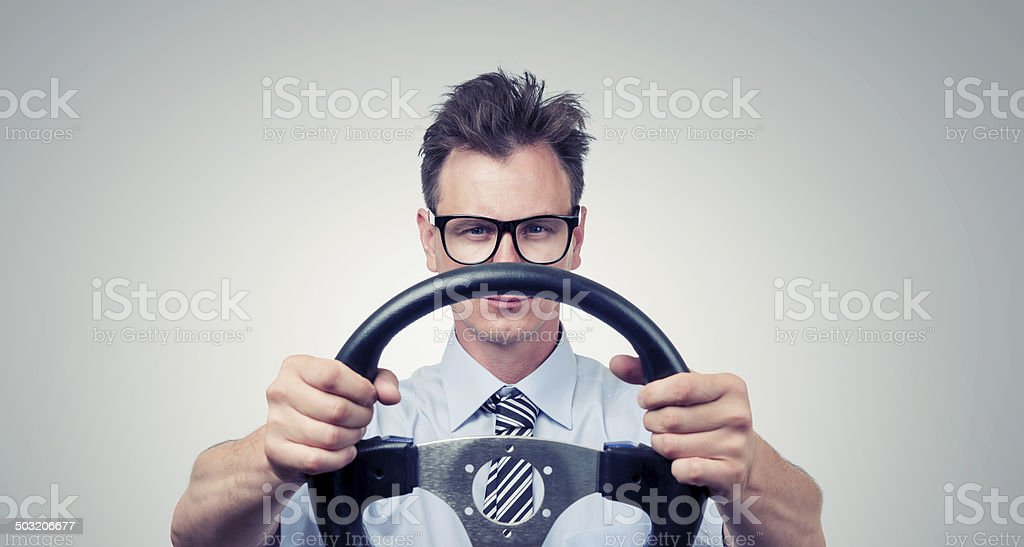 Funny businessman in glasses with a steering wheel stock photo