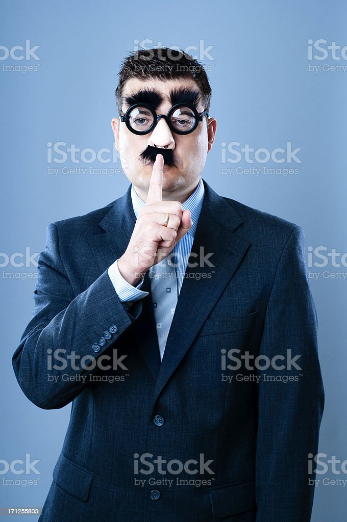 Funny businessman makes a sign to be quiet stock photo