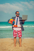 Portrait of funny businessman on the beach. Man having fun by the sea. Summer vacation and travel concept