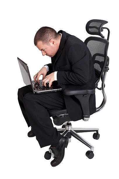 A funny businessman sitting in an awkward position stock photo