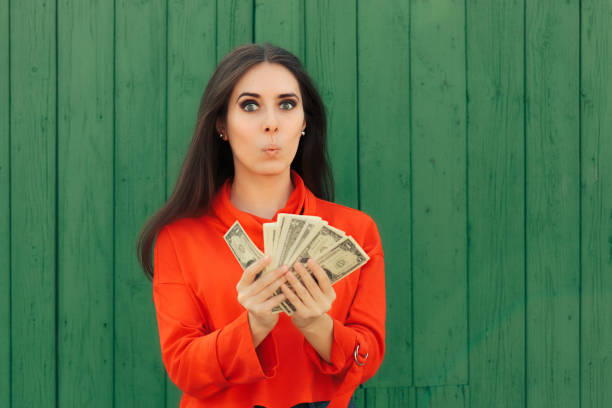 Funny Casual Girl Holding Money Thinking to Invest – zdjęcie