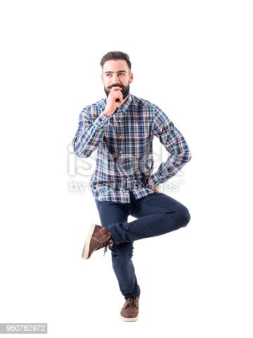 istock Funny charming bearded young man sitting in mid air on one leg 950782972