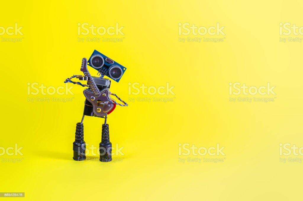 Drôle joyeux mignon charmant robot joue de la guitare sur fond jaune - Photo