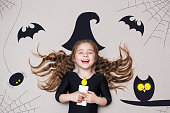 istock Funny child dressed witch costume. Halloween holidays concept 1016155010