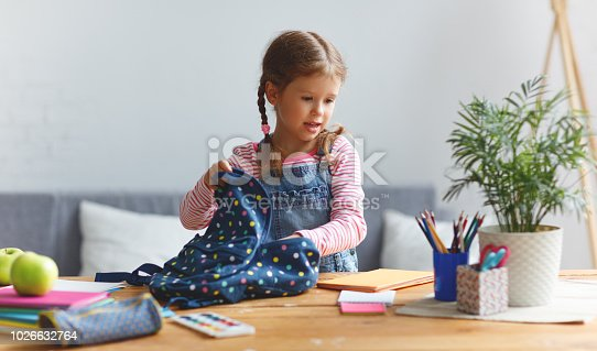 istock funny child  girl  doing homework writing and reading at home 1026632764