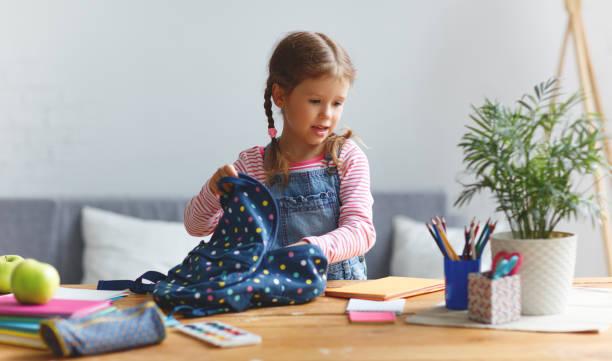 Lustiges Kind Mädchen tun Hausaufgaben schreiben und lesen zu Hause – Foto