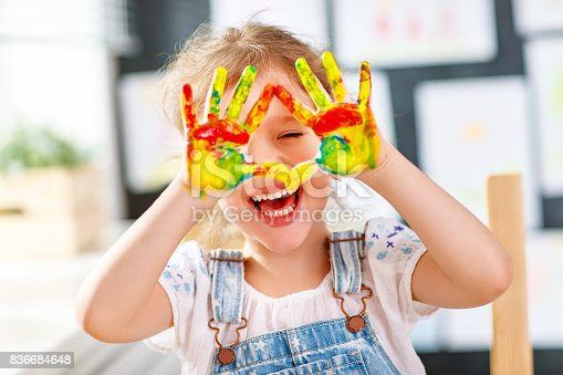 istock funny child girl draws laughing shows hands dirty with paint 836684648