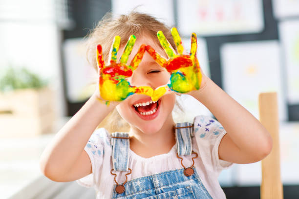 lustiges kind mädchen zieht lachend zeigt hände schmutzig mit farbe - kinderfarben stock-fotos und bilder