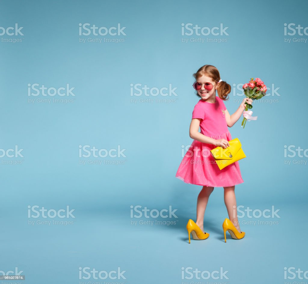 funny child girl fashionista in big mother's   shoes on colored background - foto stock