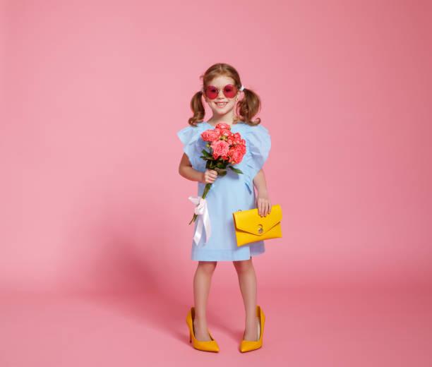 lustiges kind mädchen fashionista in großen mutter schuhe auf farbigem hintergrund - kinderhandtaschen stock-fotos und bilder