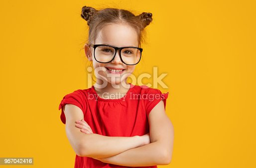 istock funny child girl in glasses on colored background 957042416
