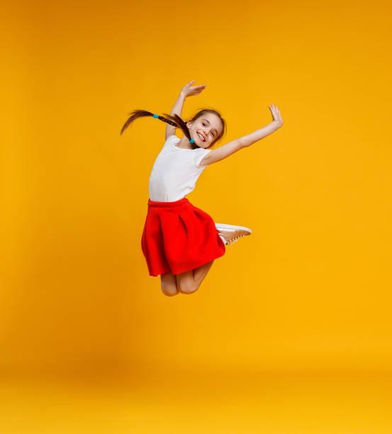 niña divertida saltando sobre fondo amarillo de color - saltar actividad física fotografías e imágenes de stock