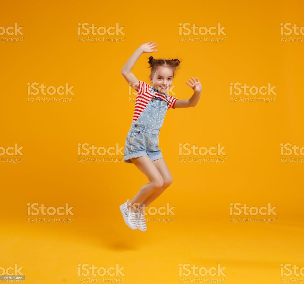 funny child girl jumping on colored yellow background - Zbiór zdjęć royalty-free (Codzienne ubranie)