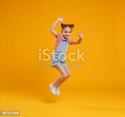 istock funny child girl jumping on colored yellow background 957042558