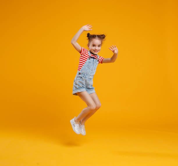 面白い子女の子色黄色背景にジャンプ ストックフォト