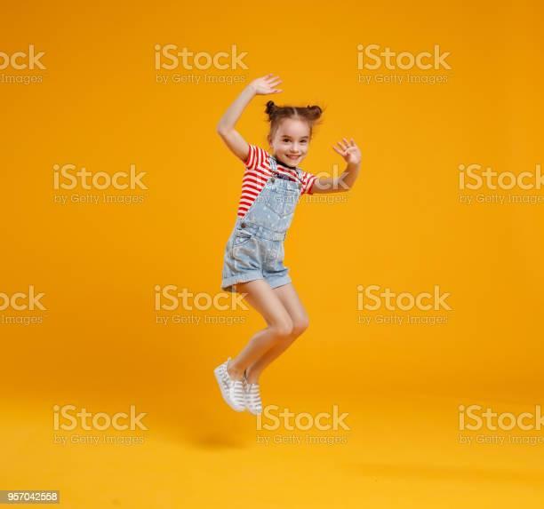 Funny Child Girl Jumping On Colored Yellow Background - zdjęcia stockowe i więcej obrazów Codzienne ubranie