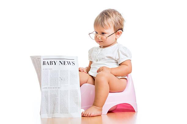 funny child girl reading newspaper on chamberpot stock photo