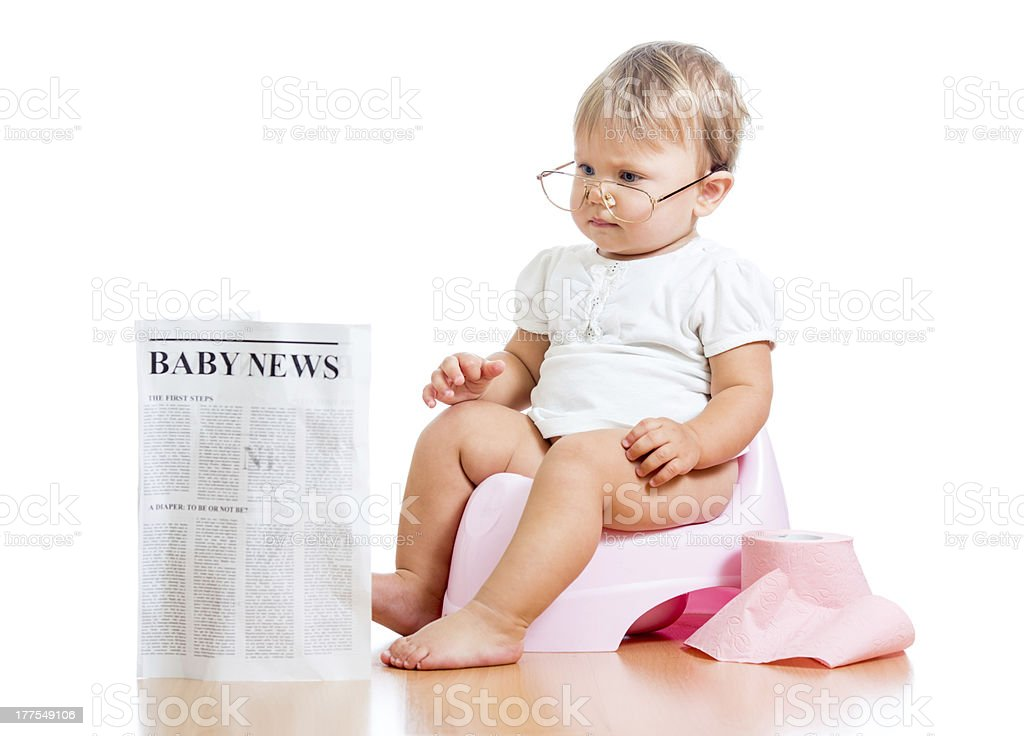 funny child girl reading newspaper on chamberpot royalty-free stock photo