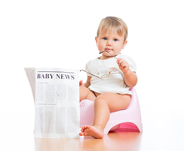 funny child girl sitting on chamberpot with eyeglasses and newsp stock photo