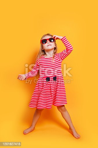 604367022 istock photo funny child girl wearing sunglasses and red dress on a orange background 1201627415