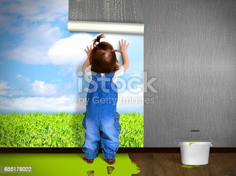 istock Funny child hanging wallpaper, doing repairs. Eco house concept. 655176022