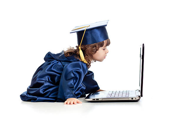 funny child in academician clothes using laptop stock photo