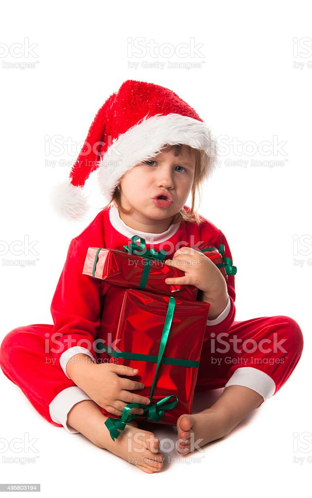 f6e4d29b3348d funny child in Santa red hat holding Christmas gifts royalty-free stock  photo
