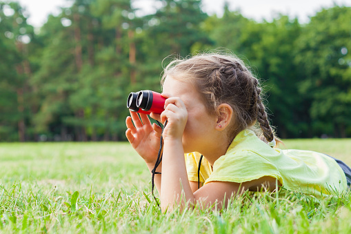 Funny child little girl looking through binoculars on sunny summer day.  Lifestyle, happy summertime, summer camp, Active family time on nature. Hiking with little kids.