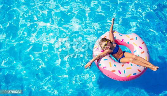 Funny Little Girl Playing On Inflatable Donut In Pool