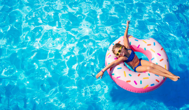 Funny Child On Inflatable Donut In Pool stock photo