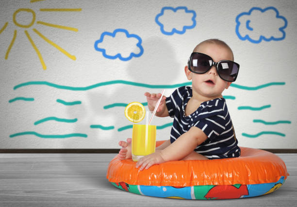 Funny child on swimming ring at home. Beach rest concept stock photo