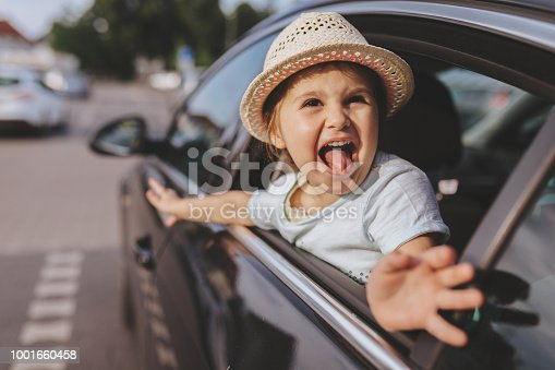 Cute and lovely toddler girl with a hat, sitting on a backseat, smiling through a car window.
