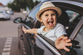 Funny child riding on a backseat of a car
