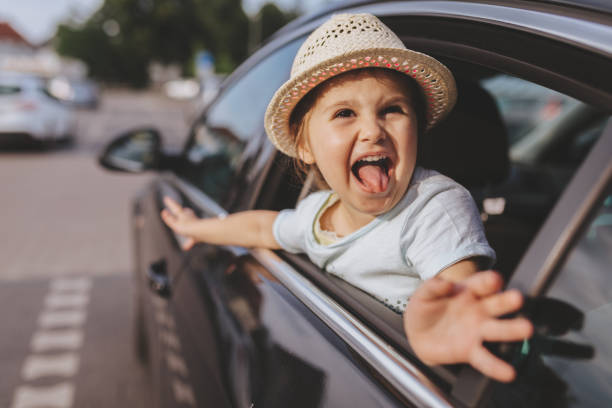 Funny child riding on a backseat of a car Cute and lovely toddler girl with a hat, sitting on a backseat, smiling through a car window. protruding stock pictures, royalty-free photos & images