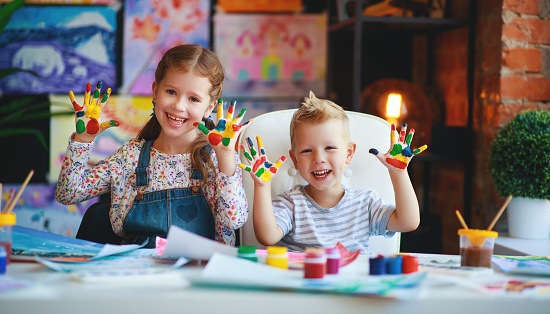 1019302738 istock photo funny children girl  and boy draws laughing shows hands dirty with paint 1165205555