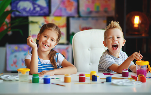 1019302738 istock photo funny children girl  and boy draws laughing   with paint 1166436571