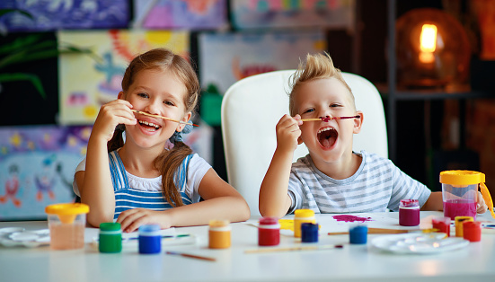 1019302738 istock photo funny children girl  and boy draws laughing   with paint 1169296275