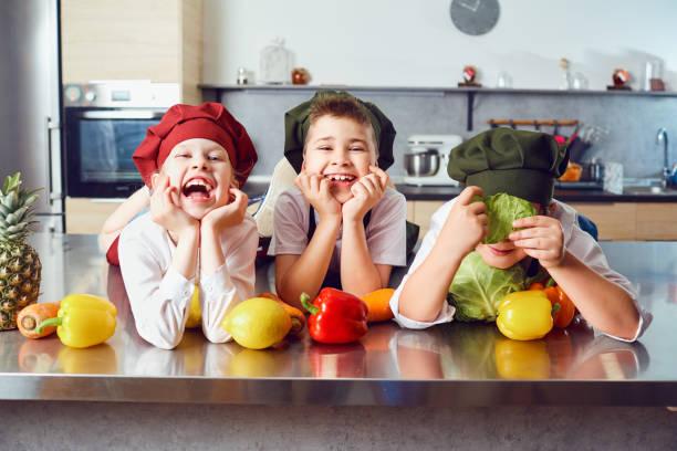 Lustige Kinder in der Uniform der Köche in der Küche – Foto