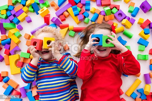istock Funny children playing with colorful blocks. 590142876