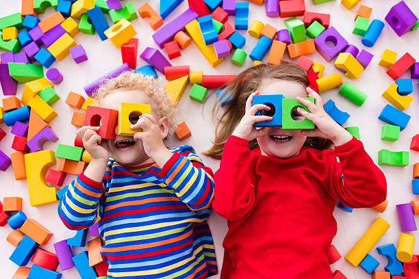 funny children playing with colorful blocks. - preschool building stock photos and pictures