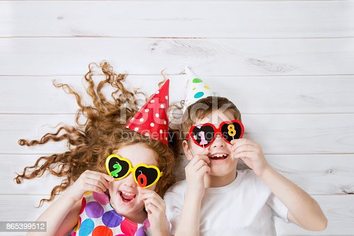 865399512istockphoto Funny children with sunglasses, hold 2018 candles 865399512