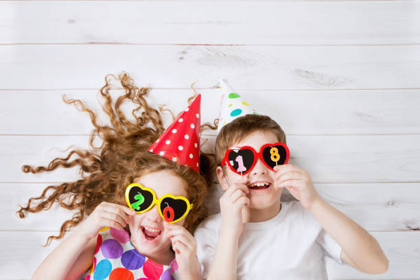 Funny children with sunglasses, hold 2018 candles stock photo