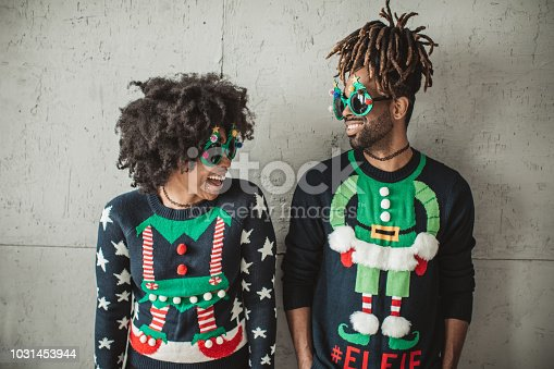 Young couple celebrating Christmas at home. They wear   christmas sweaters and funny glasses.