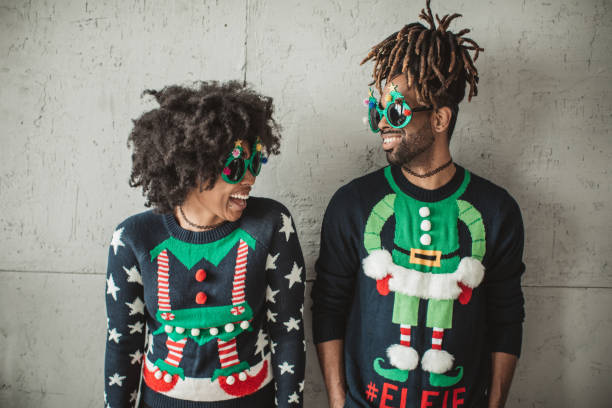 Funny Christmas couple Young couple celebrating Christmas at home. They wear   christmas sweaters and funny glasses. ugliness stock pictures, royalty-free photos & images